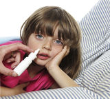 Ill little girl using nasal spray Royalty Free Stock Photo