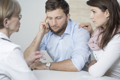Ill man and assisting wife. Ill men and assisting wife ad doctor's office Royalty Free Stock Image