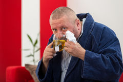 Ill man blowing his nose with paper napkin and drinking tea at home Stock Photography
