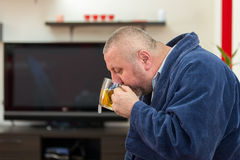 Ill man blowing his nose with paper napkin and drinking tea at home Royalty Free Stock Images
