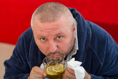 Ill man blowing his nose with paper napkin and drinking tea at home Royalty Free Stock Photo