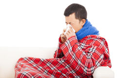 Ill man blowing nose with tissue on sofa Royalty Free Stock Images