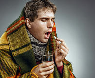 Ill Man covered with plaid blanket take medicine pill with a glass of water . Stock Photos