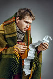 Ill Man covered with plaid blanket take medicine tablets according to instructions. Stock Photo