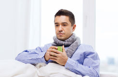 Ill man with flu drinking hot tea from cup at home Stock Photo