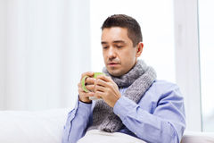 Ill man with flu drinking hot tea from cup at home Royalty Free Stock Image