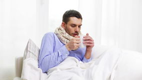 Ill man with flu drinking hot tea at home Royalty Free Stock Photo