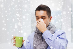 Ill man with flu drinking tea and blowing nose. Healthcare, flu, people, rhinitis and medicine concept - ill man blowing his nose with paper napkin and drinking Stock Images