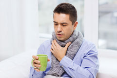 Ill man with flu drinking tea and coughing at home. Healthcare, people and medicine concept - ill man with flu coughing and drinking hot tea from cup at home Royalty Free Stock Images
