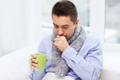 Ill man with flu drinking tea and coughing at home. Healthcare, people and medicine concept - ill man with flu coughing and drinking hot tea from cup at home Royalty Free Stock Photo