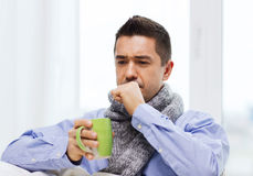 Ill man with flu drinking tea and coughing at home. Healthcare, people and medicine concept - ill man with flu coughing and drinking hot tea from cup at home Stock Photography