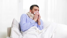 Ill man with flu at home sneezing and blowing nose Royalty Free Stock Photo