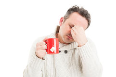 Ill man holding tea mug and suffering a migraine Royalty Free Stock Images