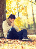 Ill man with paper tissue in autumn park Royalty Free Stock Photo