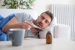 Sick man checking temperature and feeling bad at home stock photos