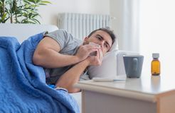 Sick man blowing nose and feeling bad at home stock photography