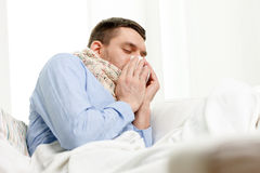 Ill man in scarf blowing nose at home Stock Photo