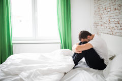 An Ill man sitting on his bed at home Royalty Free Stock Photo