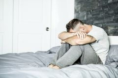 Ill man sitting on his bed Stock Photo