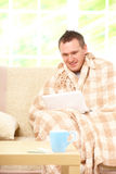 Ill man sitting on sofa Royalty Free Stock Photography