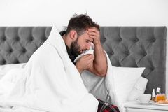Ill man suffering from cough. At home stock photography