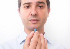 Ill man taking a blue medicine capsule Stock Images
