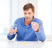 Ill man taking his pills at home. Health, healthcare, medicine, medication, drugs, concept - ill man taking his pills at home Royalty Free Stock Images