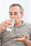 Ill man taking medication sitting up holding a glass of water Royalty Free Stock Photography