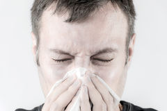 Ill man with tissue is sneezing Royalty Free Stock Photo