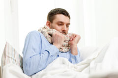 Ill man wearing scarf lying in bed at home Stock Photo