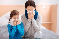 Ill mother and daughter sneezing together. Sneezing relatives. Tired ill mother sitting with her little ill kid and sneezing stock photography