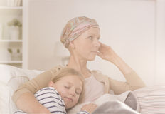 Mother after chemotherapy embracing child. Ill mother with headscarf after chemotherapy embracing her sleeping child royalty free stock image