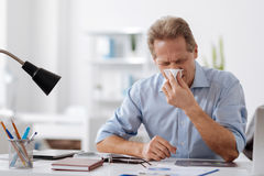 Ill office worker blowing his nose Stock Photos