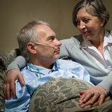 Ill old man lying bed with wife. Seriously ill old men lying in bed with loving wife Royalty Free Stock Images