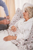 Ill older woman in bed. Ill older women in bed and her caring husband Stock Images