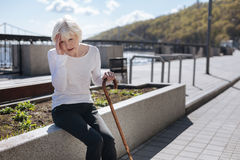 Ill pensioner having terrible pain in her head outside Royalty Free Stock Photography