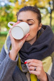 Ill sad girl with hot drink and medicine in the park. Autumn tim Royalty Free Stock Images