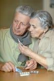 Ill senior couple with pills Stock Photos
