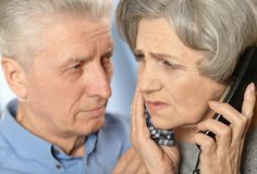 Ill senior couple. Portrait of a beautiful sad senior couple with telephone Royalty Free Stock Photo