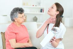 Ill senior female with pain and carer giving instructions stock image