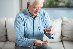 Ill senior man taking pill. And drinking water Stock Photos