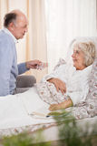 Ill senior woman in bed. Ill senior women in bed and assisting husband Stock Photography