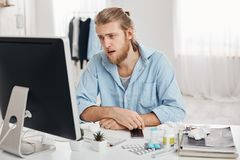 Ill or sick bearded male dressed in blue shirt with tired and suffering face expression, being allergic, having health Royalty Free Stock Photos
