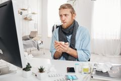 Ill sick bearded male sits in front of computer screen with thermometer in mouth, measures temperature, holds a cup of. Ill or sick bearded male manager sits in stock photos