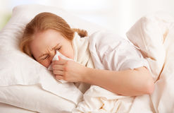 Ill sick young woman sneezes  into a handkerchief in bed. Ill sick young woman sneezes and blows her nose into a handkerchief in bed Royalty Free Stock Image