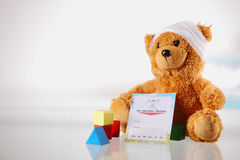 Ill Teddy Bear with Card and Shape Blocks on Table Royalty Free Stock Images