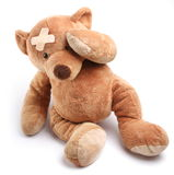 Ill teddy bear with plaster on its head. Isolated on a white background Royalty Free Stock Photos