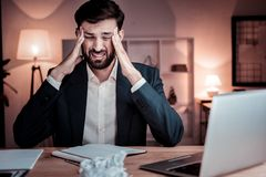 Ill unshaken man sitting and having head ache. Unexpected pain. Ill unshaken stylish man sitting in the office holding hands near head and having head ache Stock Photography