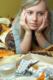Ill woman. Ill , sad woman in bad and pills royalty free stock photography
