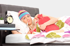 Ill woman in bed with a thermometer in her mouth Royalty Free Stock Images